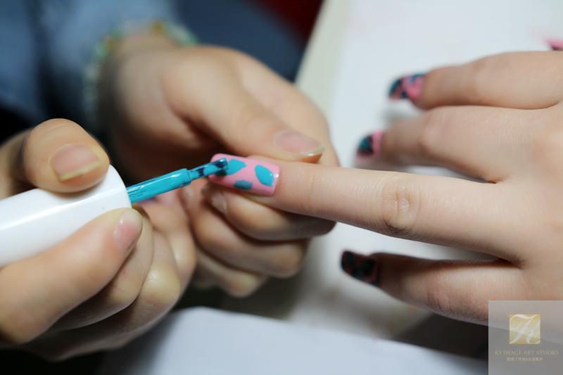 导语:马上夏天到了,姐妹们都轻装上阵了,那一身的清爽再配上一双美美的指甲岂不让人眼前一亮,时尚感大增,今天北京志诚化妆美甲培训学校:段娟教大家一款由豹纹延生出来的一款时尚美甲:小清新的甲油胶彩绘,简单易学,时尚百搭。 首先,我们需要准备的工具材料有: 粉色甲油胶,绿色甲油胶,黑色甲油胶,小亮片甲油胶,勾线笔等 一、在做好基础护理的甲面上均匀涂抹粉色甲油胶,并且照干30秒,颜色要饱和,可二次涂抹。  二、再使用绿色甲油胶画出花纹,花纹要两头尖,有规律排序,一个甲面上不宜过多,两三个点缀即可,然后照灯30秒。
